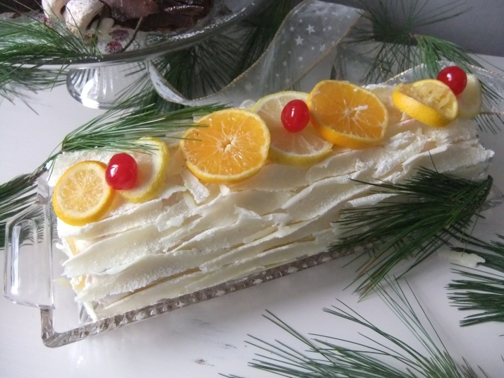 Vanilla Cake with a Tutti-Frutti Cherry and Peach Filling, Frosted with a Vanilla Buttercream and decorated with a Vanilla-Coconut Bark.