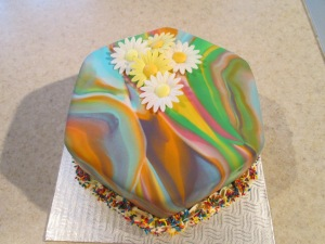 Tye Dye Mocha Cake with layers of Chocolate Whipped Cream, Frosted in Swiss Buttercream and covered in Fondant.